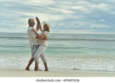 Happy elderly  couple  dancing  on  tropical beach