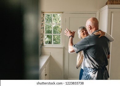 Happy elderly couple dancing together holding each other. Romantic senior couple having fun doing ballroom dancing at home.