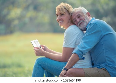 Happy elderly couple enjoying spending time together, hugging, talking with smiling face and laughing in the park, spending time, health care and relaxing time concept.