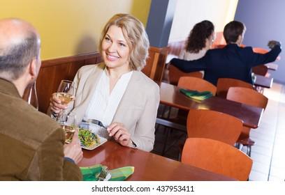 Happy elderly couple having dinner at restaurant table