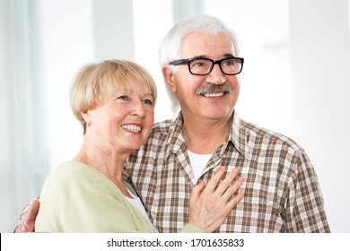 Happy elderly couple hugging at home and smiling