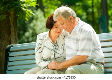 Happy elderly couple listening music in headset or praying together, outdoors