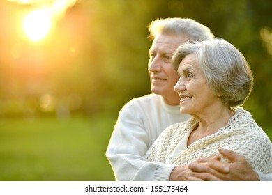 Happy elderly couple at nature on leaves and sunset background