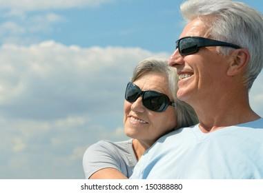 Happy elderly couple on a sky background