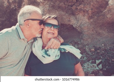Happy elderly couple on vacation in Tenerife with white hair and sunglasses smile and kiss each other on the cheek