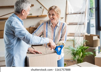 happy elderly couple packing cardboard boxes during relocation