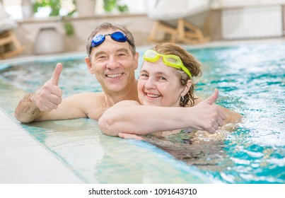 happy elderly couple in the pool showing thumbs up.