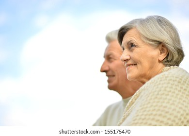 Happy elderly couple posing against the sky