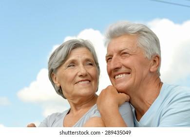 Happy elderly couple posing against the sky