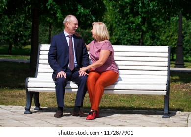 Happy Elderly couple resting on a bench in summer park