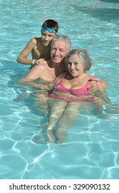Happy Elderly couple resting at pool water together with grandson