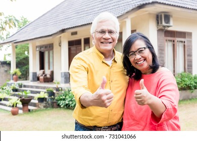 Happy elderly couple showing thumbs up in front of their new residential property