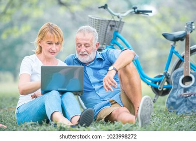 Happy elderly couple sitting on the green grass together and enjoying using laptop for online entertainment in the park, watching movie, listening music, spending time and relaxing time concept.
