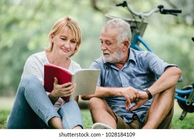 Happy elderly couple with smiling face enjoying together, reading a book in the park, spending time and relaxing time concept.