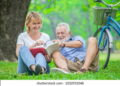 Happy elderly couple with smiling face enjoying together, reading a book with magnifying glass in the park, spending time and relaxing time concept.