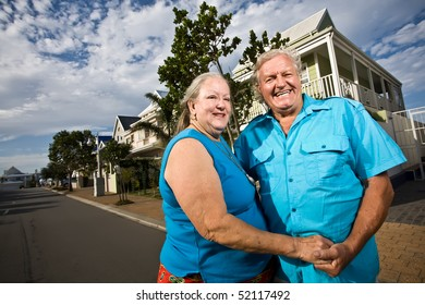 A happy elderly couple standing in the road in front of a house