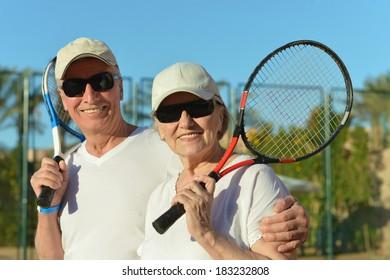 Happy elderly couple with tennis racket in hand