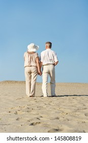happy elderly couple walking barefoot on the sand in the summer
