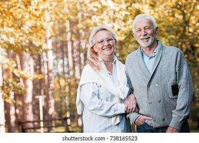 Happy elderly couple walking outdoors in nature