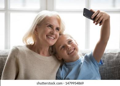 Happy elderly grandmother and little granddaughter using phone taking selfie, schoolchild grandkid raise hand make self portrait with loving granny, multi-generational people modern tech usage concept