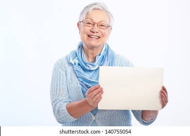 Happy elderly lady holding blank sheet in hand, smiling.