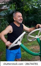 Happy elderly man doing exercises on urban district sports ground