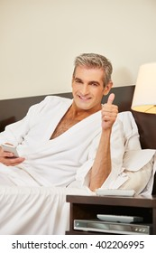 Happy elderly man in hotel room holding his thumbs up