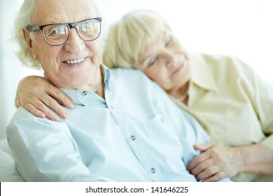 Happy elderly man looking at camera with his wife on background
