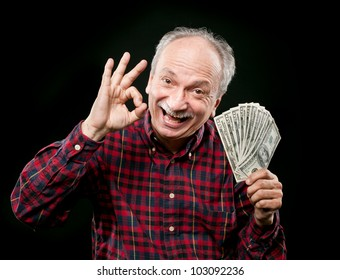 Happy elderly man showing fan of money and sign OK with fingers