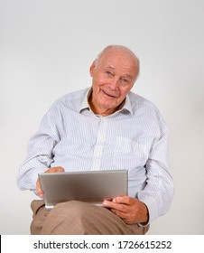 happy elderly man sits on a chair and works with his laptop