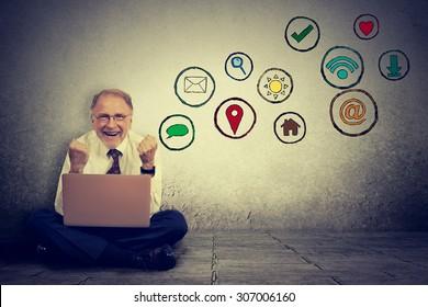 Happy elderly man working on computer using social media application