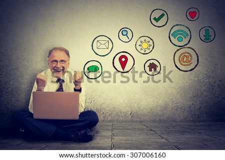 Happy elderly man working on computer using social media application