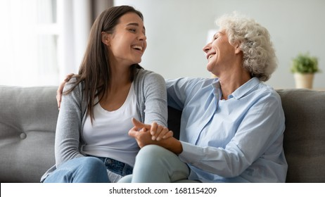 Happy elderly mother and grown-up daughter sit on couch laugh talk and joke in living room, overjoyed millennial girl and elderly mom have fun relax enjoy family leisure weekend at home