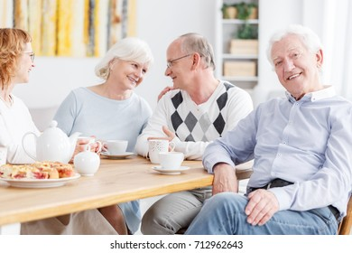 Happy elderly people spending time together at nursing home, senior man smiling at camera with friends chatting in the background