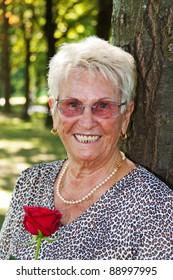 happy elderly senior citizen holding a red rose.
