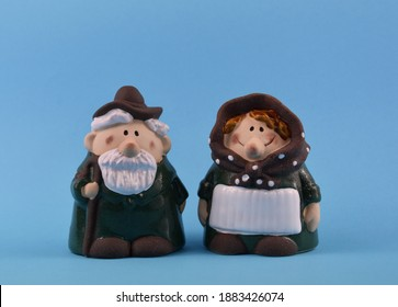 Happy elderly senior couple ceramic figurine stock images. Cute grandpa and grandma statuette images. Senior couple in love images. Pensioners isolated on a blue background