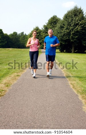 Happy elderly senior couple jogging in park.