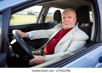 Happy elderly senior man driving a car - looking in camera, wide angle