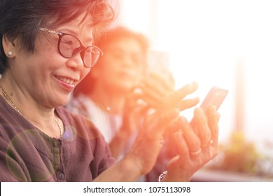 Happy elderly senior people society lifestyle concept. Ageing Asia women using smartphone share social media together in wellbeing county home.