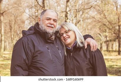Happy Elderly Senior Romantic Couple holding hands in nature, Old people portrait outdoor winter autumn season.