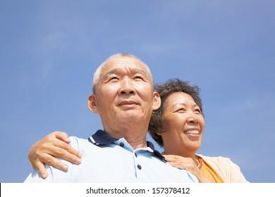Happy elderly seniors couple with cloud background
