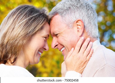 Happy elderly seniors couple in park. Love.