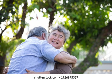 Happy elderly Southeast Asian couple embracing in park on sunny day, Senior Couple Anniversary or love together in Valentines day concept