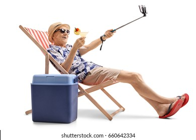 Happy elderly tourist with a cocktail sitting in a sun lounger and taking a selfie isolated on white background