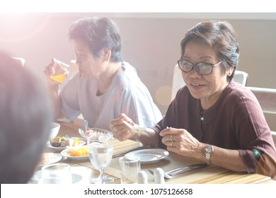 Happy elderly twin senior people society lifestyle concept. Ageing Asia women having dinner on dining table together in hospice older wellbeing nursing home community.