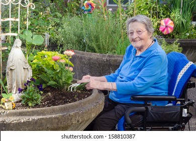 A happy elderly woman in an assisted-living facility tends to her flowers in a wheelchair-accessible garden container.