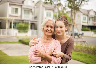 Happy elderly woman with a caregiver in the garden, Home care concept.