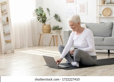 Happy Elderly Woman Choosing Online Tutorials On Laptop For Training At Home, Sitting On Yoga Mat On Floor In Living Room