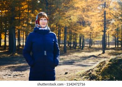 happy elderly woman in a dark coat in autumn in the woods, autumn forest
