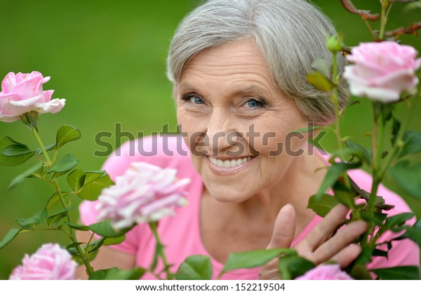 Happy elderly woman enjoying beautiful pink roses outdoors